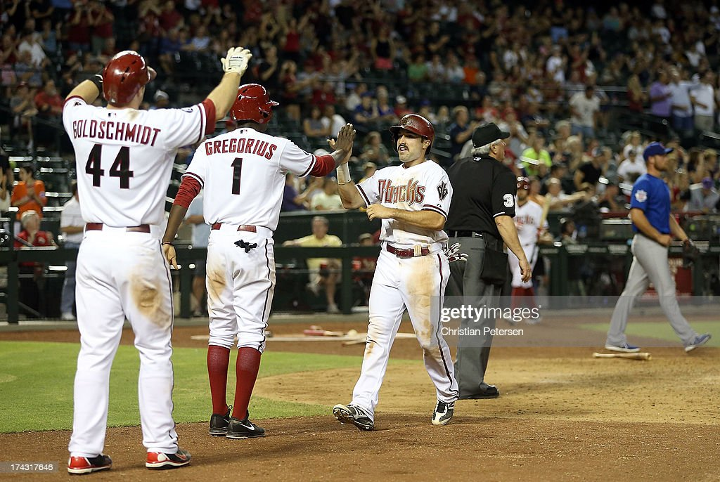 <a gi-track='captionPersonalityLinkClicked' href=/galleries/search?phrase=Adam+Eaton&family=editorial&specificpeople=210898 ng-click='$event.stopPropagation()'>Adam Eaton</a> #6 of the Arizona Diamondbacks high-fives Didi Gregorius #1 and <a gi-track='captionPersonalityLinkClicked' href=/galleries/search?phrase=Paul+Goldschmidt&family=editorial&specificpeople=7511120 ng-click='$event.stopPropagation()'>Paul Goldschmidt</a> #44 after scoring an eighth inning run against the Chicago Cubs during the MLB game at Chase Field on July 23, 2013 in Phoenix, Arizona.