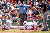 Adam Eaton of the Chicago White Sox slides to evade the tag of Rick Porcello of the Boston Red Sox as he scores on a passed ball during the first...