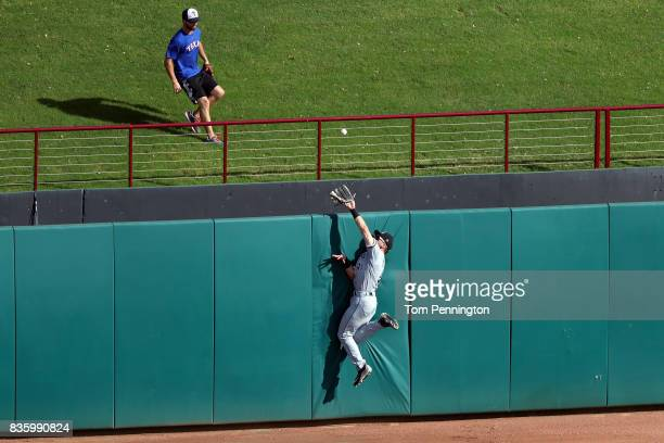 Adam Engel of the Chicago White Sox climbs the outfield wall while trying to field a tworun home run hit by Rougned Odor of the Texas Rangers in the...