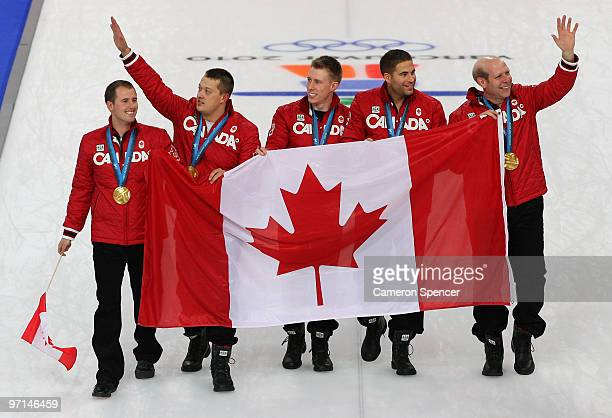 Adam Enright Ben Hebert Marc Kennedy John Morris and Kevin Martin of Canada walk on the ice with the Canadian flag and their gold medals after the...