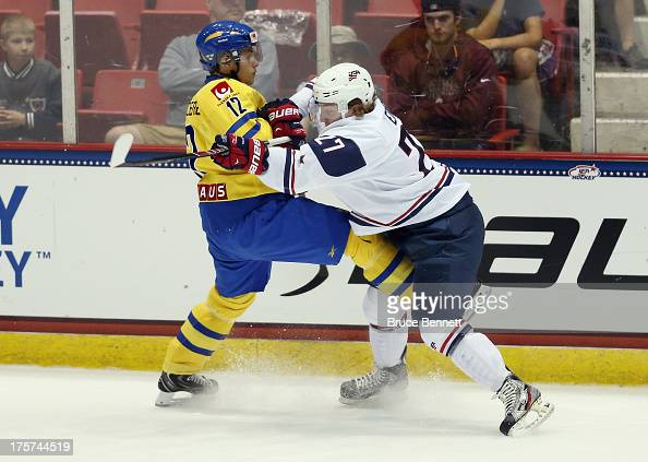 Adam Erne of Team USA checks Arvid Lundberg of Team Sweden during the 2013 USA Hockey Junior Evaluation Camp at the Lake Placid Olympic Center on...