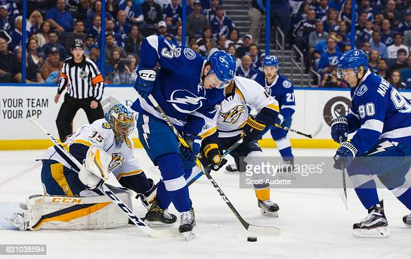 Adam Erne of the Tampa Bay Lightning skates against Nashville Predators goalie Pekka Rinne and Ryan Ellis at Amalie Arena on January 5 2017 in Tampa...