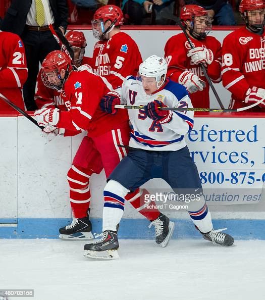 Adam Erne of the USA National Junior Team checks Mike Moran of the Boston University Terriers during NCAA exhibition hockey at Walter Brown Arena on...