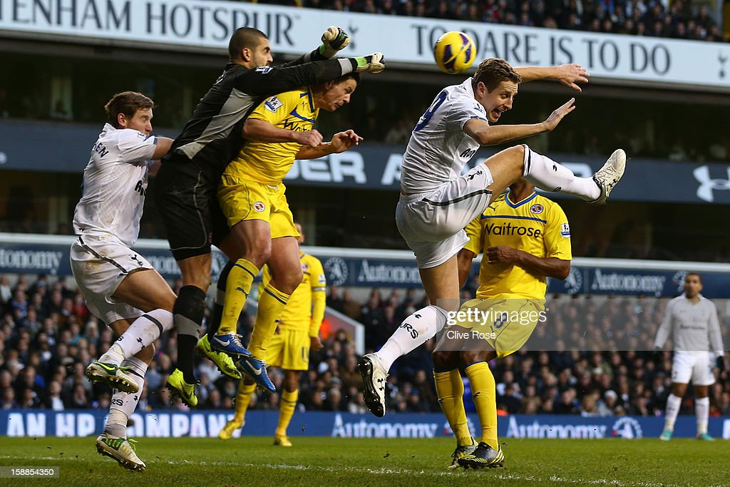 Adam Federici of Reading punches the ball clear of Michael Dawson of Tottenham Hotspur during the Barclays Premier League match between Tottenham Hotspur and Reading at White Hart Lane on January 1, 2013 in London, England.