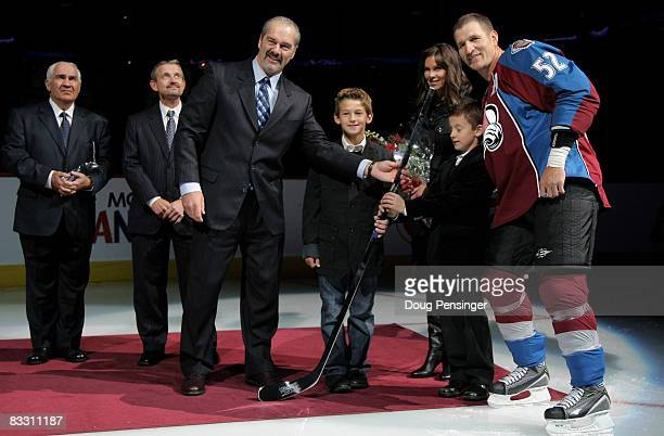 Adam Foote of the Colorado Avalanche is honored for playing in his 1000th career game along with his wife Jennifer and sons Callan and Nolan as he...