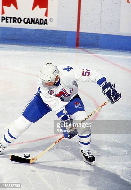 Adam Foote of the Quebec Nordiques stick handles during an NHL game in November 1992 at the Quebec Coliseum in Quebec City Quebec Canada
