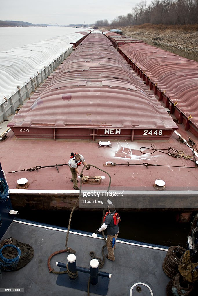 Adam Foushee, a deckhand, bottom, throws a rope to Dustin Declue, first mate, as they secure 15 grain barges to the Capt. Bill Stewart tow boat in the Mississippi River outside St. Louis, Missouri, U.S., on Thursday, Dec. 6, 2012. Barges carrying grain, soybeans, coal, oil and other commodities on the Mississippi River have started to reduce their loads to navigate waters shrunk by the worst drought in 50 years. Photographer: Daniel Acker/Bloomberg via Getty Images