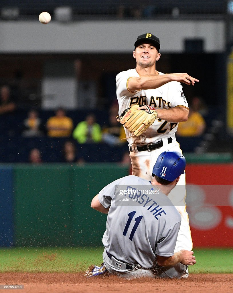 Adam Frazier #26 of the Pittsburgh Pirates attempts to turn a double play against Logan Forsythe #11 of the Los Angeles Dodgers in the sixth inning during the game at PNC Park on August 22, 2017 in Pittsburgh, Pennsylvania.