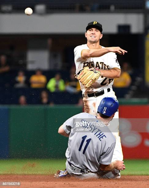 Adam Frazier of the Pittsburgh Pirates attempts to turn a double play against Logan Forsythe of the Los Angeles Dodgers in the sixth inning during...
