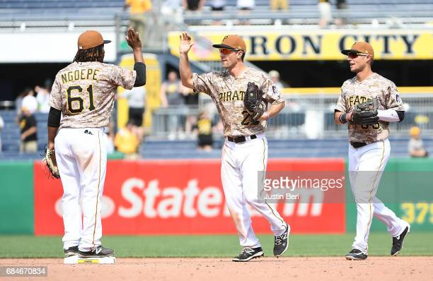 Adam Frazier of the Pittsburgh Pirates celebrates with Gift Ngoepe and Danny Ortiz after the final out in the Pittsburgh Pirates 104 win over the...