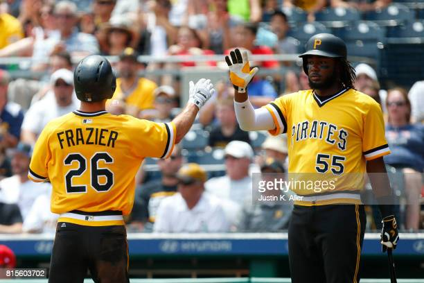 Adam Frazier of the Pittsburgh Pirates celebrates with Josh Bell of the Pittsburgh Pirates after scoring on a RBI single in the first inning against...