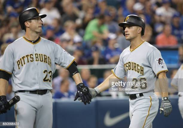 Adam Frazier of the Pittsburgh Pirates is congratulated by David Freese after scoring a run in the third inning during MLB game action against the...