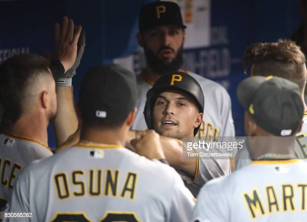 Adam Frazier of the Pittsburgh Pirates is congratulated by teammates in the dugout after scoring a run in the third inning during MLB game action...