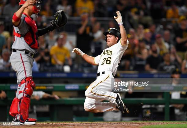 Adam Frazier of the Pittsburgh Pirates slides safely into home plate during the seventh inning against the Washington Nationals at PNC Park on May 17...
