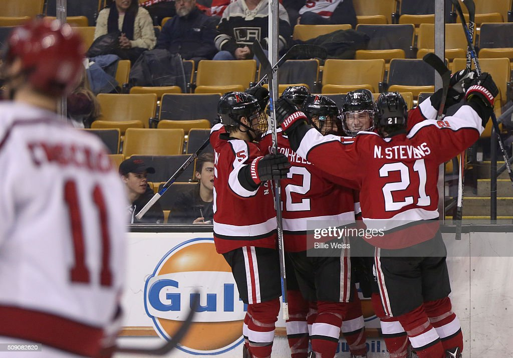 Adam Gaudette #8 of Northeastern University reacts with teammates after scoring a goal against Harvard University during the third period of the Beanpot Tournament consolation game at TD Garden on February 8, 2016 in Boston, Massachusetts.