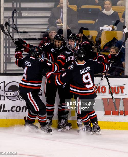 Adam Gaudette of the Northeastern Huskies celebrates after scoring a goal against the Harvard Crimson with teammates Zach AstonReese Jeremy Davies...