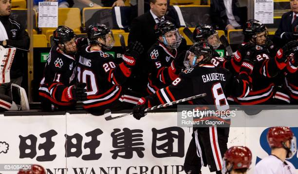 Adam Gaudette of the Northeastern Huskies celebrates after scoring a goal against the Harvard Crimson with teammates during NCAA hockey in the...