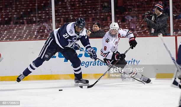 Adam Gaudette of the Northeastern Huskies is checked by Anthony Wyse of the New Hampshire Wildcats during NCAA hockey at Fenway Park during 'Frozen...
