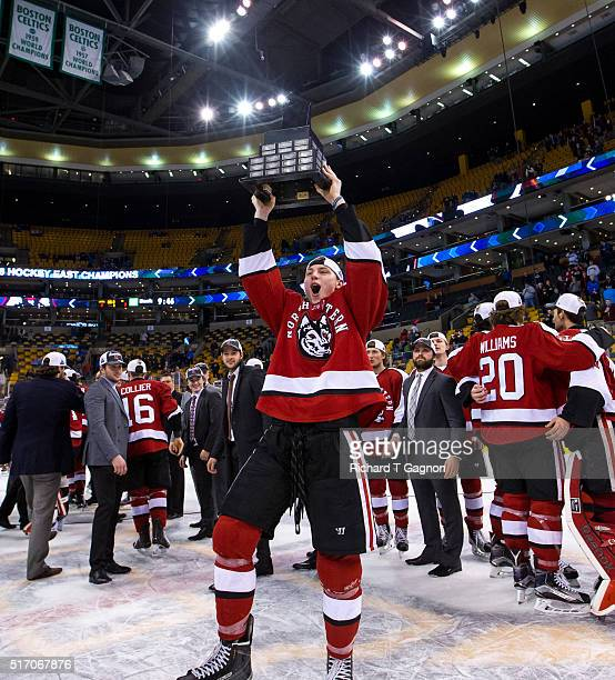 Adam Gaudette of the Northeastern Huskies raises the Lamoriello Trophy as he celebrates a 32 victory against the Massachusetts Lowell River Hawks...