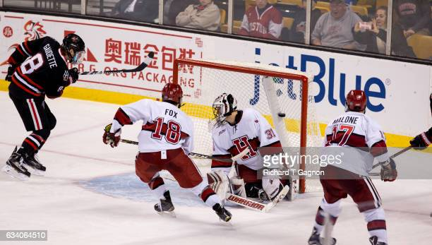 Adam Gaudette of the Northeastern Huskies scores a goal against Merrick Madsen of the Harvard Crimson during NCAA hockey in the semifinals of the...