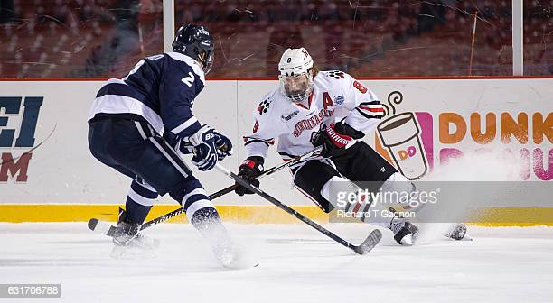 Adam Gaudette of the Northeastern Huskies skates against Matias Cleland of the New Hampshire Wildcats during NCAA hockey at Fenway Park during...