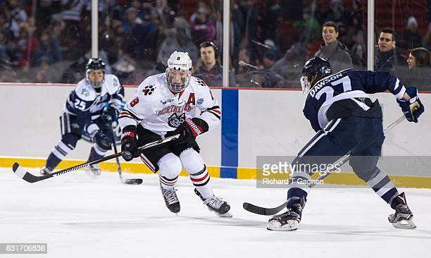 Adam Gaudette of the Northeastern Huskies skates against Matt Dawson of the New Hampshire Wildcats during NCAA Hockey at Fenway Park during 'Frozen...