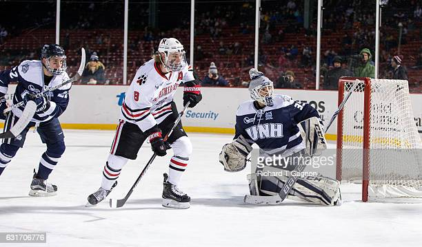 Adam Gaudette of the Northeastern Huskies skates near the crease in front of Daniel Tirone of the New Hampshire Wildcats at Fenway Park during...
