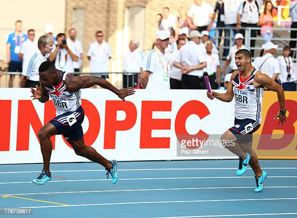 Adam Gemeli of Great Britain hands over the baton to team mate Harry AikinesAryeetey during the Men's 4x100 metres final during Day Nine of the 14th...