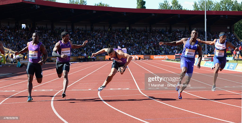 Adam Gemili of Great Britain falls as he crosses the finish line as Marvin Bracy of USA wins the Men's100m Final during the Sainsbury's Birmingham...