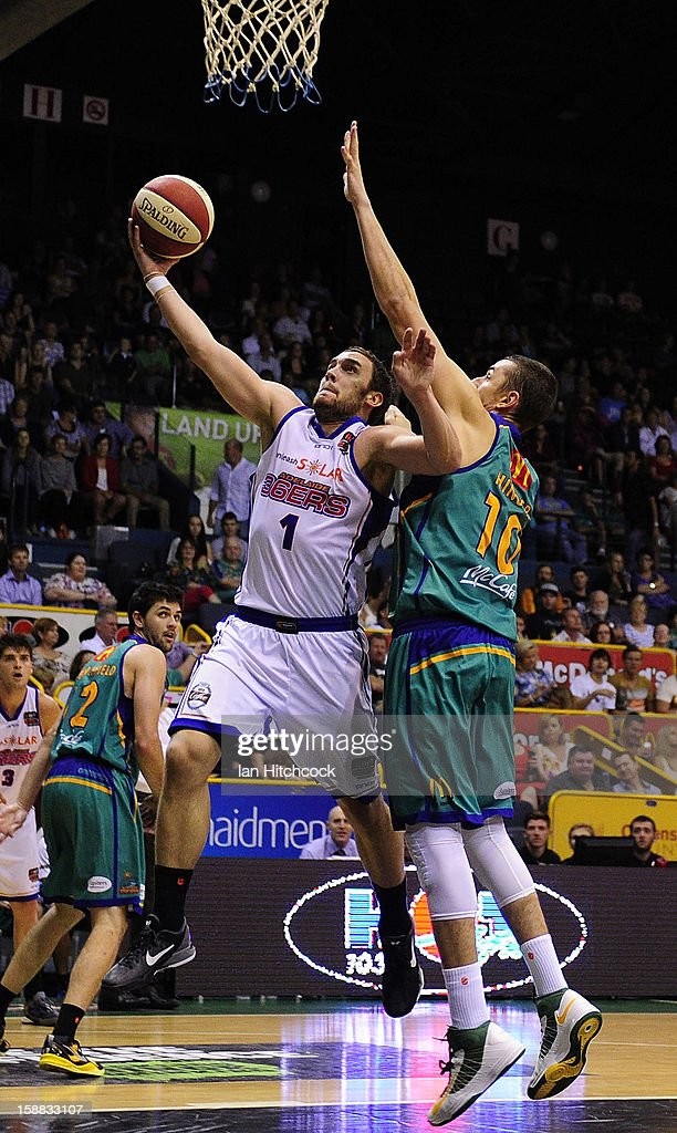 Adam Gibson of the 36ers makes a layup past Russell Hinder of the Crocodiles during the round 12 NBL match between the Townsville Crocodiles and the Adelaide 36ers at Townsville Entertainment Centre on December 31, 2012 in Townsville, Australia.