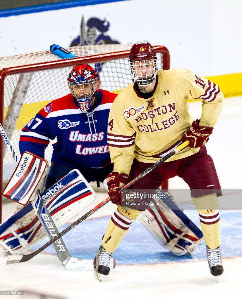 Adam Gilmour #14 of the Boston College Eagles stands in front of Connor Hellebuyck #37 of the Massachusetts Lowell River Hawks during the NCAA Division I Men's Ice Hockey Northeast Regional Championship Final at the DCU Center on March 30, 2014 in Worcester, Massachusetts.