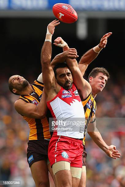 Adam Goodes of the Swans attempts to mark infront of Josh Gibson and Ben Stratton of the Hawks during the 2012 AFL Grand Final match between the...