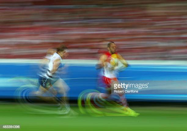 Adam Goodes of the Swans runs with the ball during the round 19 AFL match between the Geelong Cats and the Sydney Swans at Simonds Stadium on August...
