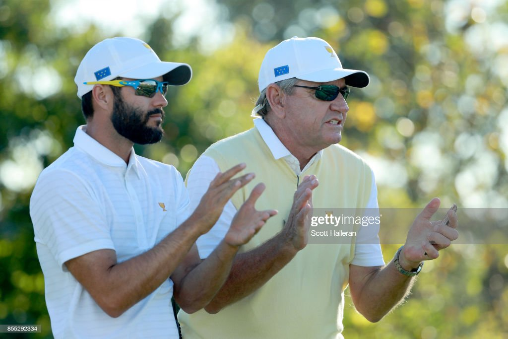 Adam Hadwin and Nick Price of Zimbabwe and Captain of the International Team react during the Thursday foursomes matches of the first round of the Presidents Cup at Liberty National Golf Club on September 28, 2017, in Jersey City, New Jersey.