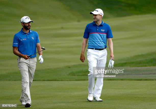 Adam Hadwin of Canada and Russell Knox of Scotland walk up the 16th fairway during the third round of the World Golf Championships Bridgestone...