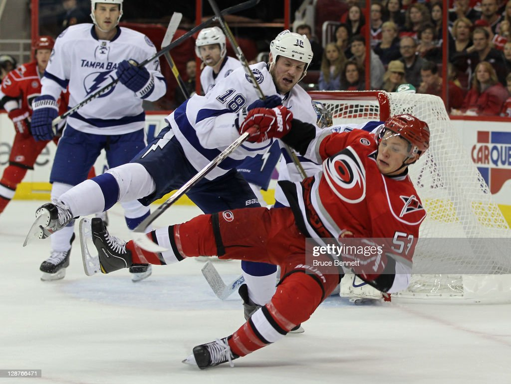 Adam Hall of the Tampa Bay Lightning knocks Jeff Skinner of the Carolina Hurricanes off the puck at the RBC Center on October 7 2011 in Raleigh North...