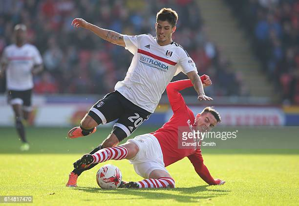 Adam Hammill of Barnsley slides under Lucas Piazon of Fulham in a tackle during the Sky Bet Championship match between Barnsley and Fulham at Oakwell...