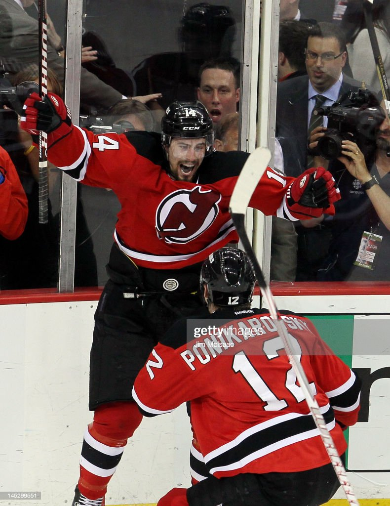 Adam Henrique of the New Jersey Devils celebrates with teammate Alexei Ponikarovsky after scoring in overtime against the New York Rangers to win...