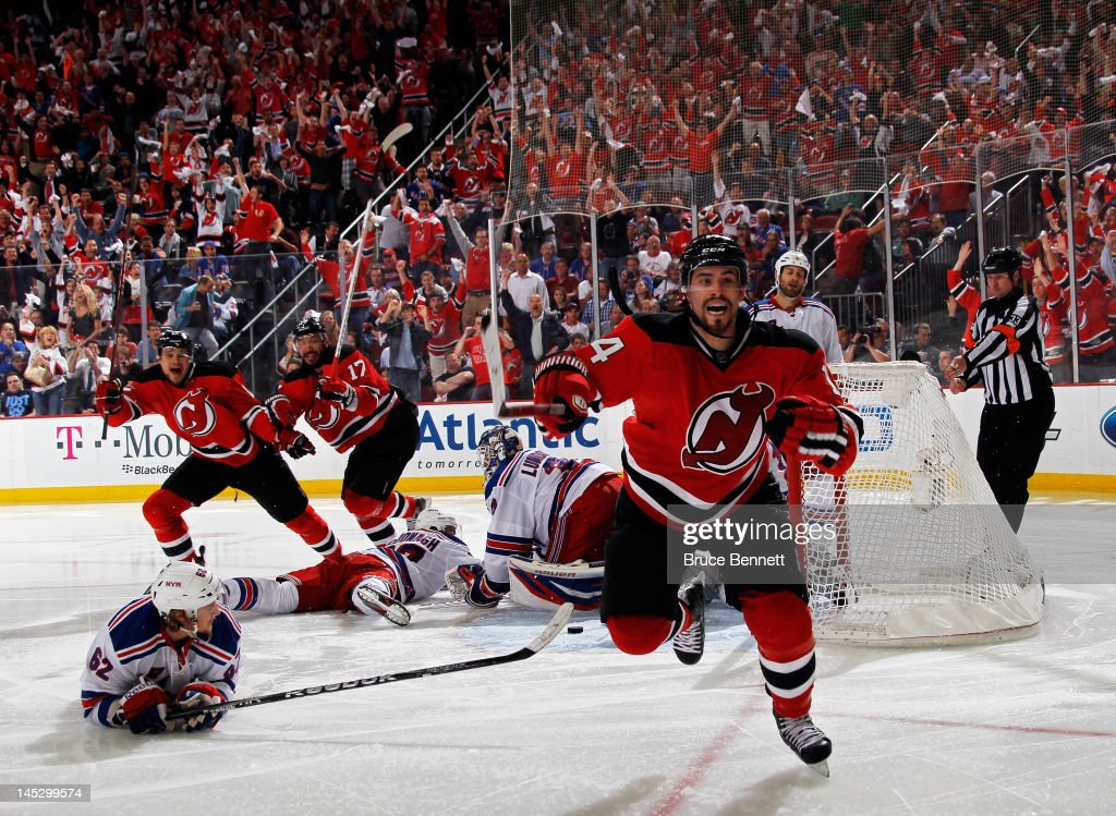 Adam Henrique of the New Jersey Devils celerbates after scoring the game winning goal in overtime against Henrik Lundqvist of the New York Rangers to...