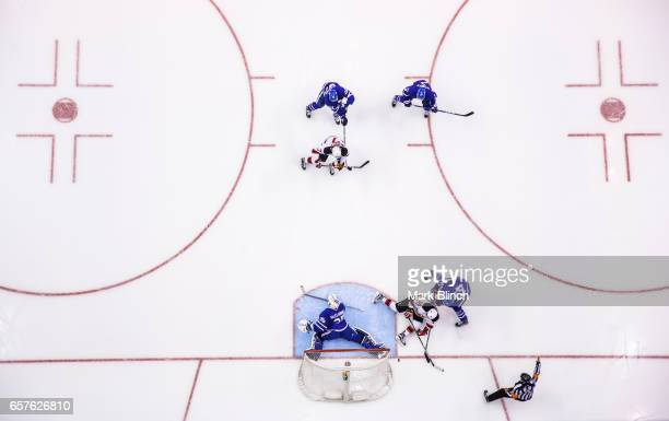 Adam Henrique of the New Jersey Devils goes to the net against Curtis McElhinney and Brian Boyle of the Toronto Maple Leafs during the first period...