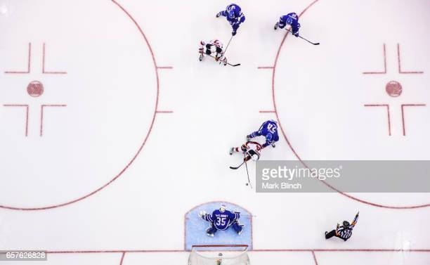 Adam Henrique of the New Jersey Devils goes to the net against Curtis McElhinney and Brian Boyle of the Toronto Maple Leafs during the third period...