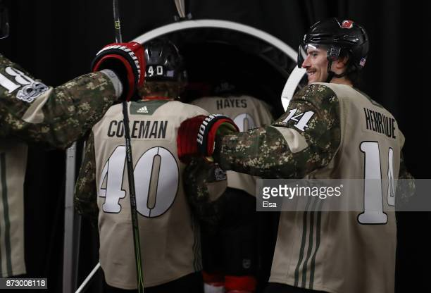 Adam Henrique of the New Jersey Devils greets Blake Coleman and the rest of his teammates as they take the ice for warm ups before the game against...