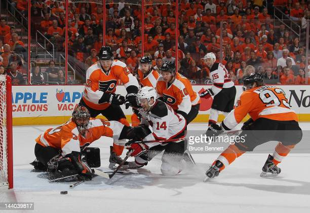 Adam Henrique of the New Jersey Devils is stopped by Ilya Bryzgalov and the Philadelphia Flyers in the first period in Game Five of the Eastern...