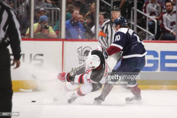 Adam Henrique of the New Jersey Devils loses his footing while skating against Sven Andrighetto of the Colorado Avalanche at the Pepsi Center on...