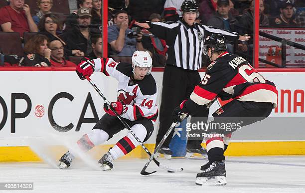 Adam Henrique of the New Jersey Devils stickhandles the puck against Erik Karlsson of the Ottawa Senators at Canadian Tire Centre on October 22 2015...