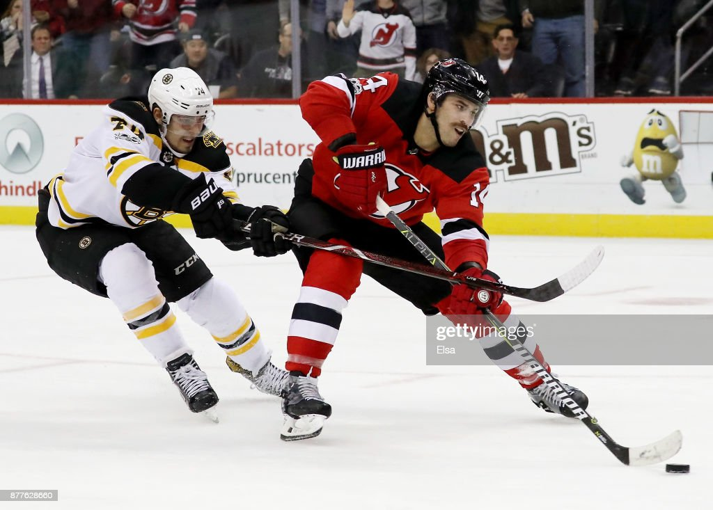 Adam Henrique #14 of the New Jersey Devils tries to get a shot in as Jake DeBrusk #74 of the Boston Bruins defends in the overtime period on November 22, 2017 at Prudential Center in Newark, New Jersey.
