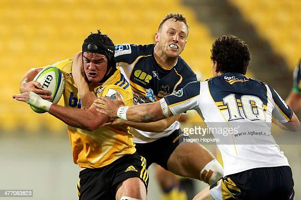 Adam Hill of the Hurricanes is tackled by Jesse Mogg of the Brumbies during the round four Super Rugby match between the Hurricanes and the Brumbies...