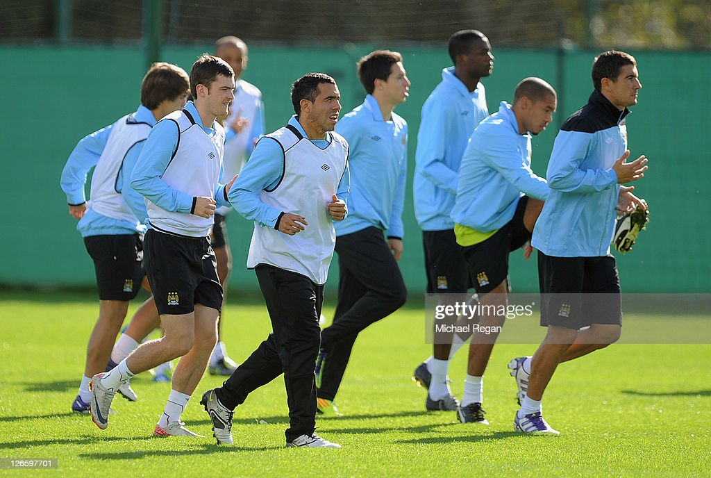 Adam Johnson (L), Carlos Tevez (2nd L) and Manchester City team-mates warm up during a training session ahead of their UEFA Champions League Group A match against Bayern Munich on September 26, 2011 in Manchester, United Kingdom.