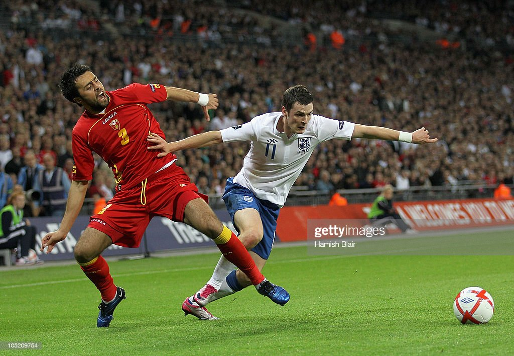 <a gi-track='captionPersonalityLinkClicked' href=/galleries/search?phrase=Adam+Johnson+-+Soccer+Player&family=editorial&specificpeople=6720094 ng-click='$event.stopPropagation()'>Adam Johnson</a> of England holds off the challenge by Marko Basa of Montenegro during the UEFA EURO 2012 Group G Qualifying match between England and Montenegro at Wembley Stadium on October 12, 2010 in London, England.