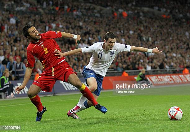 Adam Johnson of England holds off the challenge by Marko Basa of Montenegro during the UEFA EURO 2012 Group G Qualifying match between England and...